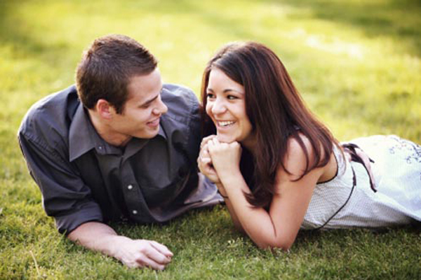 A couple sits on grass being in love