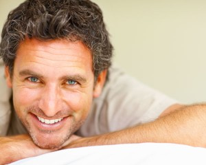 a man smiles in bed