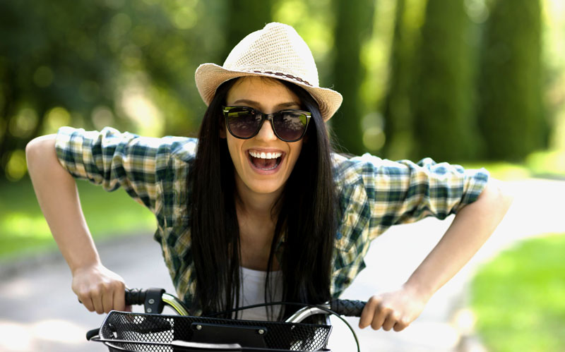 Girl wears 'ironic' hat riding a bike